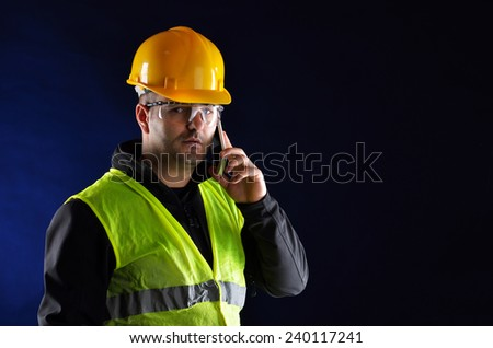 Young engineering with orange helmet talking on the phone - stock photo