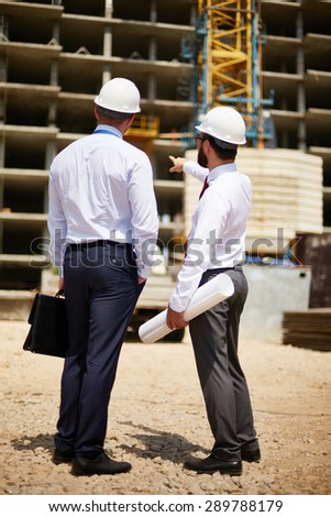 Young engineers discussing new construction at meeting - stock photo