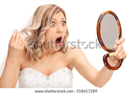 Young enraged bride looking at her hairstyle in a mirror isolated on white background - stock photo
