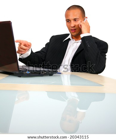 Young Entrepreneur A young businessman sitting by desk at office working on the laptop while talking on cellphone. Isolated over white. - stock photo