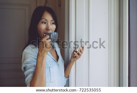 Young entrepreneur is answering business emails by a mobile phone while having break with a cup of tea. Asian woman is holding a smartphone while standing beside the window with a cup of coffee.
