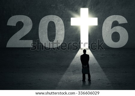Young entrepreneur looking at a door shaped a cross symbol and numbers 2016 - stock photo