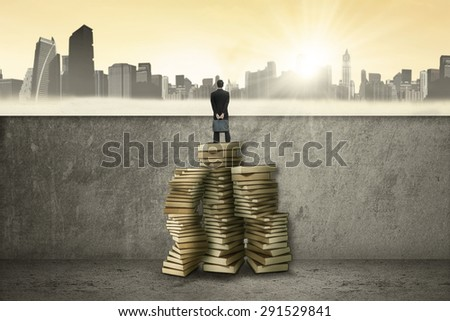 Young entrepreneur standing on a stair made of books and look at the city - stock photo
