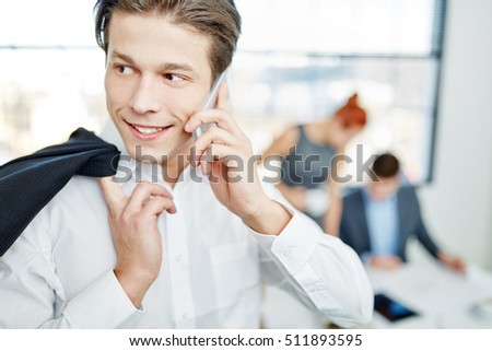 Young entrepreneur with smartphone listening and communicating