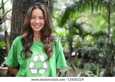 young environmental activist  in the forest wearing a green recycle t-shirt - stock photo