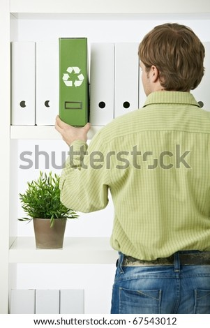 Young environmentalist man pulling out green folder from office shelf.? - stock photo