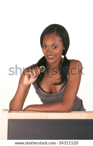 Young ethnic black female college student with condom by school chalkboard. Can be used as template for sex education themed posters or invitations - stock photo