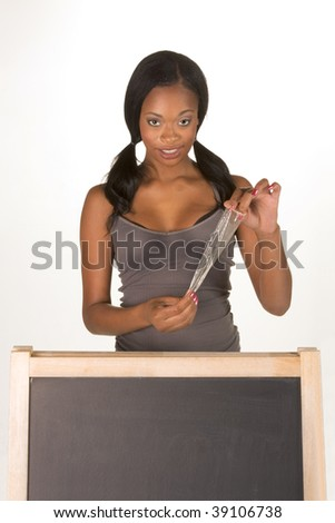 Young ethnic black female college student with condom by school chalkboard. Can be used as template for sex education themed posters or invitations