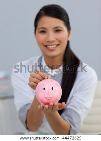 Young ethnic businesswoman saving money in a piggybank in the office - stock photo