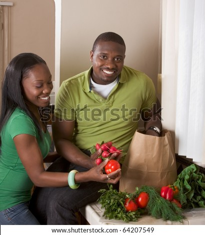 Young ethnic couple on kitchen sorting groceries - stock photo
