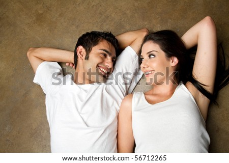 Young ethnic couple smiling to each other with love