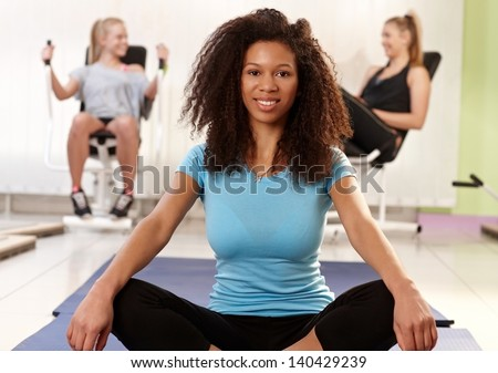 Young ethnic girl relaxing in tailor seat at the gym, smiling. - stock photo
