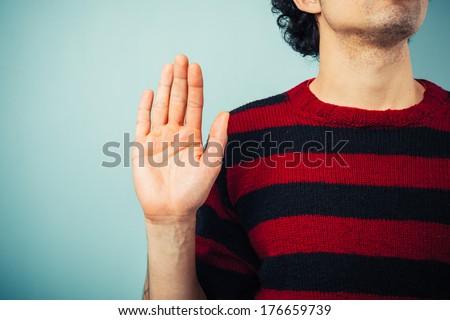 Young ethnic man is pledging allegience with his right hand raised - stock photo
