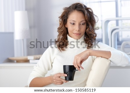Young ethnic woman drinking coffee at home, looking down.