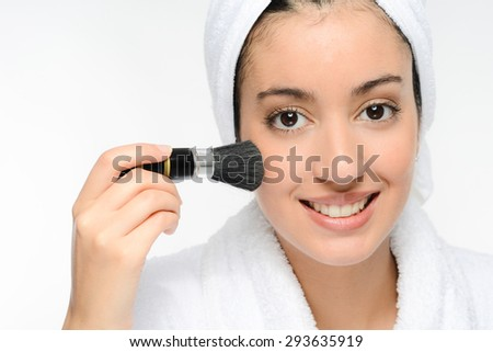 young ethnic woman in white peignoir putting on blush powder with a brush