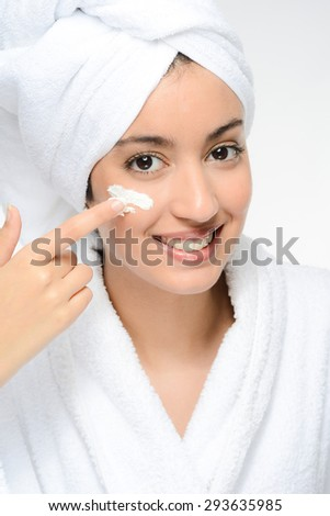 young ethnic woman in white peignoir putting on skincare facial cream