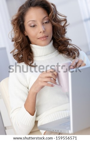 Young ethnic woman using laptop computer at home, drinking tea.