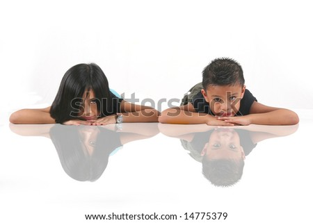 Young Eurasian Chinese Girl And Boy Laying Flat On The Floor