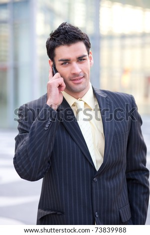 young european businessman holding his mobile phone against his ear while going through the streets - stock photo