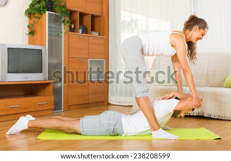 Young european couple doing regular exercises together at home