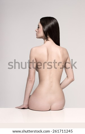 Young European fashion model woman with shiny healthy brunette hair, awesome gorgeous slim body and perfect skin is sitting on the table nude in studio for bodycare and wellness adverisement - stock photo