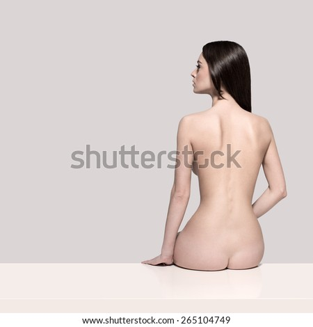 Young European fashion model woman with shiny healthy brunette hair, awesome gorgeous slim body and perfect skin is sitting on the table nude in studio for body care and wellness advertisement - stock photo