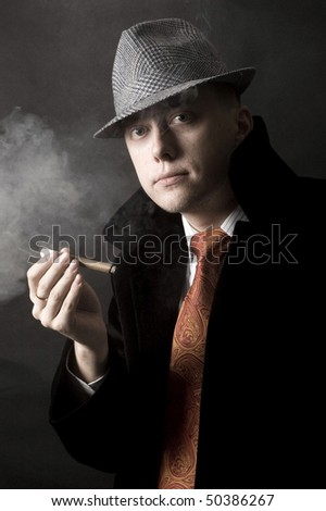 Young European gentleman with elegant clothes, tie and coat, wearing stylish hat. Smoking cigar.