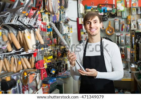 Young european male seller posing at tooling section of household store