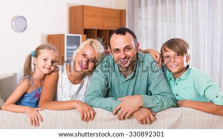 young european parents with two children posing in home interior