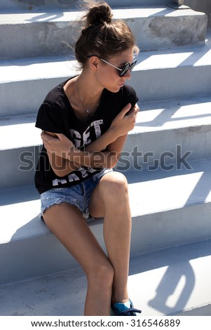 Young European teenage brunette curly model posing on stadium concrete stairs, wearing blue jeans mini shorts, sneakers, round sunglasses and black t-shirt, ready to party - stock photo
