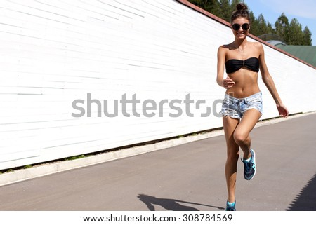 Young European teenage brunette sports model running outdoors along white wooden wall, jumping, jogging, wearing blue jeans mini shorts, sneakers, round sunglasses and black swimwear top - stock photo