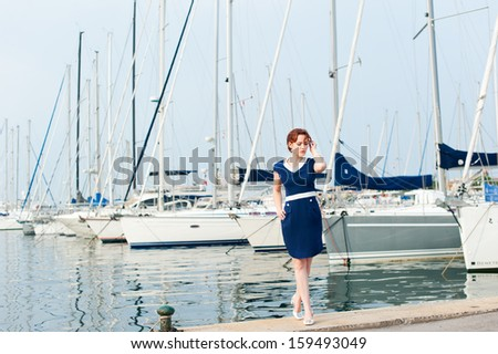 young European woman in a blue dress on the background of the pier with yachts - stock photo