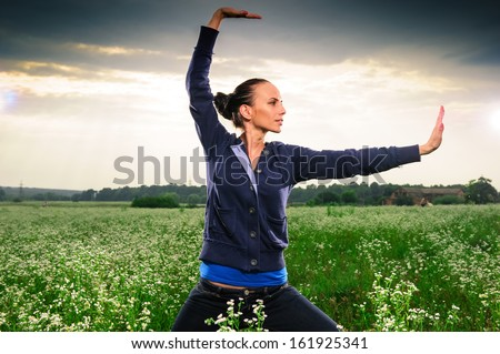 Young European woman performing yoga outdoor. - stock photo