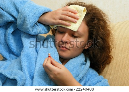 Young European woman with headache watching at pill