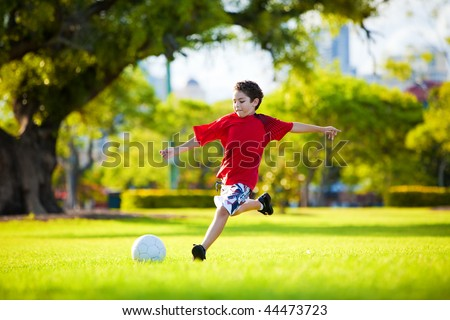 Young excited boy kicking ball in the grass outdoors - stock photo