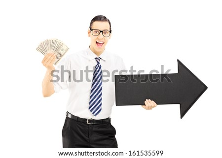 Young excited businessman holding a big black arrow pointing to the right and US dollars isolated on white background - stock photo