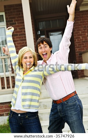 Young excited couple celebrating in front of home - stock photo