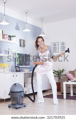 Young excited woman cleaning with a vacuum cleaner - stock photo