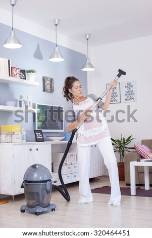 Young excited woman cleaning with a vacuum cleaner and pretending to be playing guitar