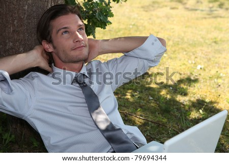 Young exec using a laptop under a tree - stock photo