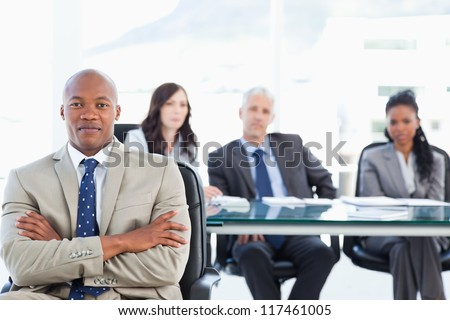 Young executive almost smiling and crossing his arms while his team is in the background