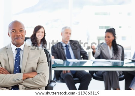 Young executive almost smiling in front of his team which is sitting in the back