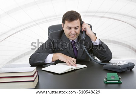 young executive at work and talking on phone at his desk at the office