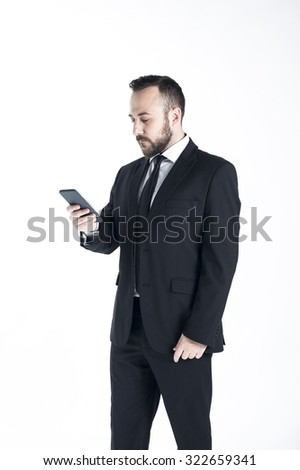 Young executive, business person, holding device with one hand, in black suite, on white background