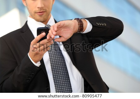 Young executive checking his watch against a cellphone - stock photo