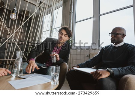 Young executive explaining something to his team in a meeting. Young man discussing business strategy with colleagues during a meeting. - stock photo