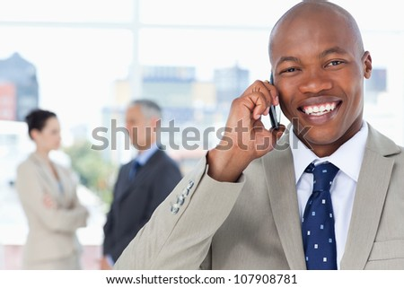 Young executive laughing while using his mobile phone - stock photo