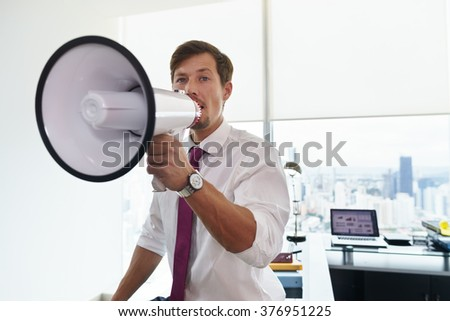 Young executive office worker holding megaphone and speaking at camera with confidence. Copy space - stock photo