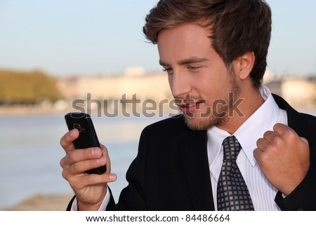 Young executive pleased with his phone message - stock photo