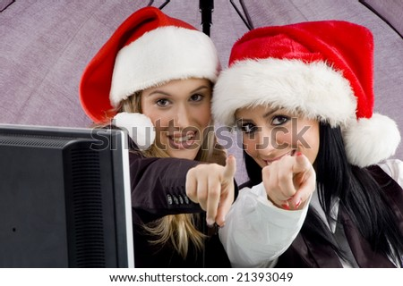 young executive pointing and wearing red christmas hat in office - stock photo
